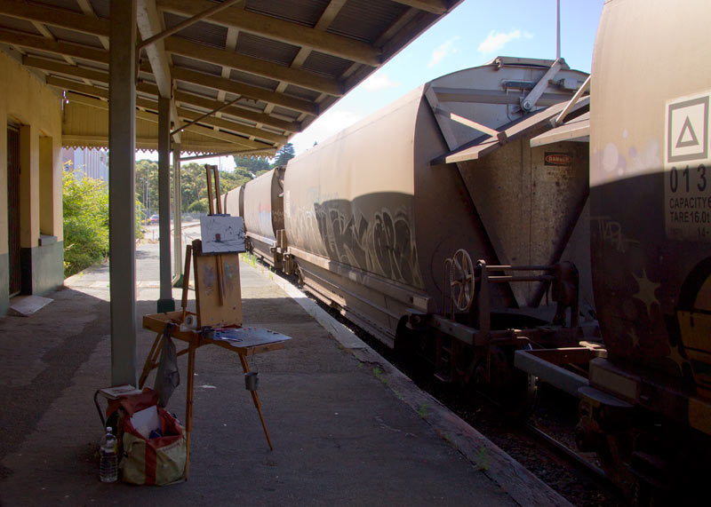 freight train blocks view of painting a railyard